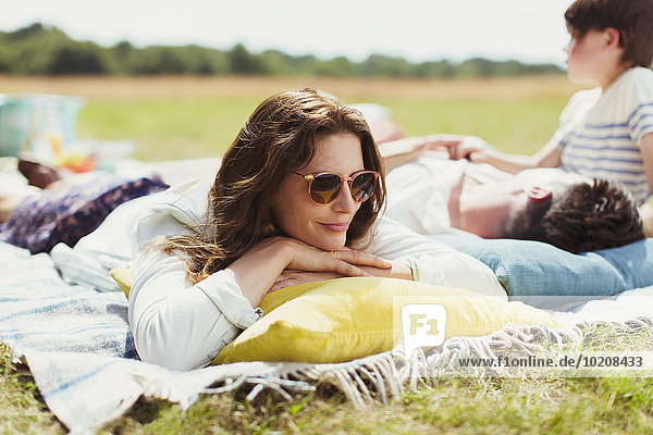 Familie entspannt auf der Decke im sonnigen Feld