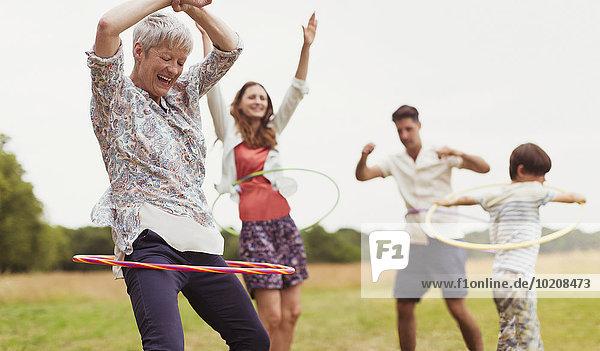 Verspieltes Mehrgenerationen-Familienspinnen in Kunststoffreifen im Feld