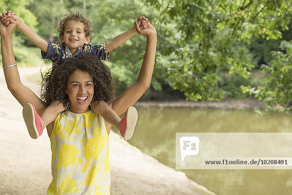 Portrait verspielte Mutter mit Sohn auf Schultern am Teich