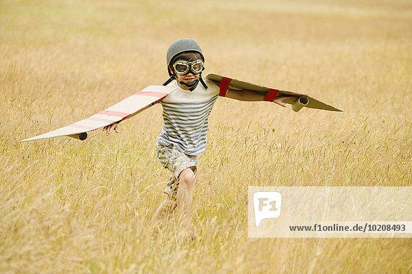 Junge rennt mit Flügeln und Fliegerhaube und Fliegerbrille im Feld
