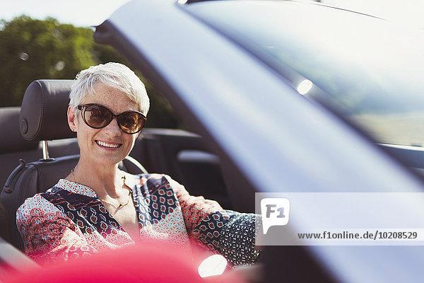 Portrait lächelnde Seniorin mit Sonnenbrille im Cabriolet