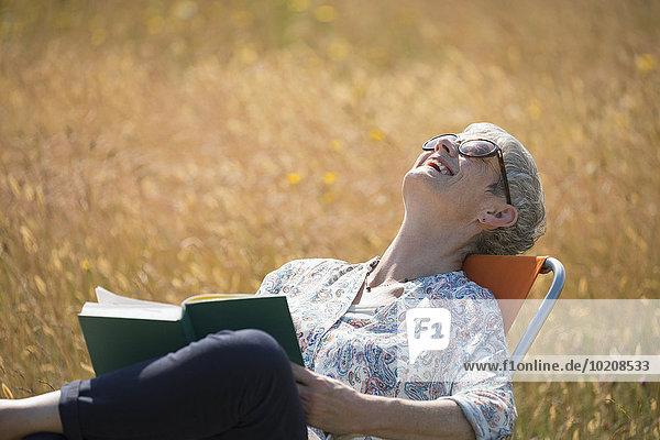 Seniorin liest Buch und lacht mit Kopf zurück im sonnigen Feld