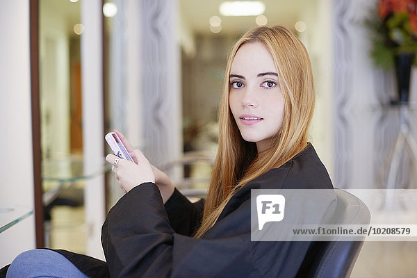 Portrait woman texting with cell phone in hair salon