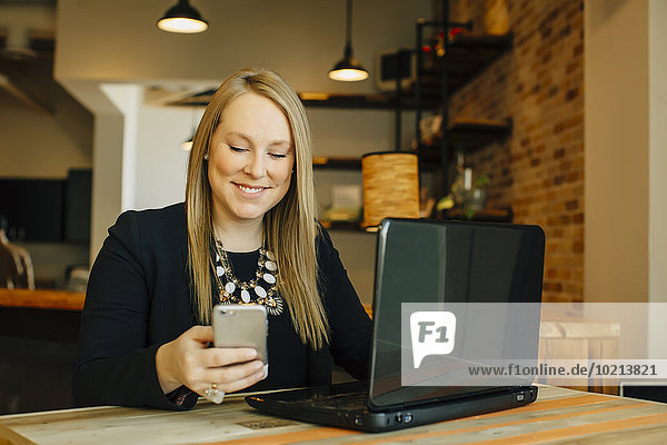 Handy benutzen Europäer Geschäftsfrau Notebook Cafe