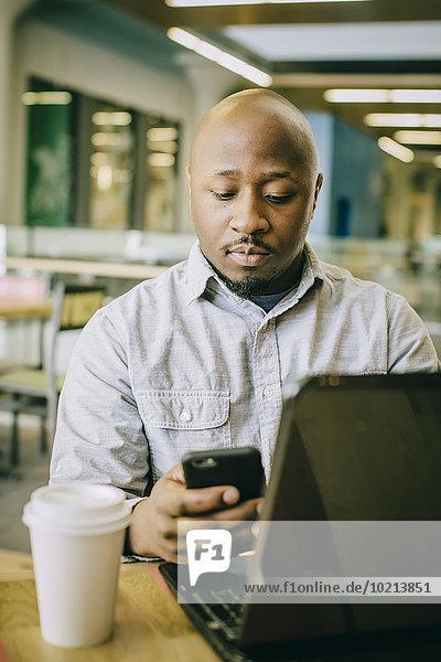 Handy benutzen Notebook Geschäftsmann Cafe schwarz