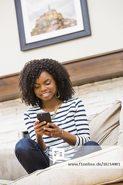 Black woman using cell phone on sofa