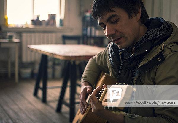 Mann Zimmer Gitarre Wohnzimmer spielen