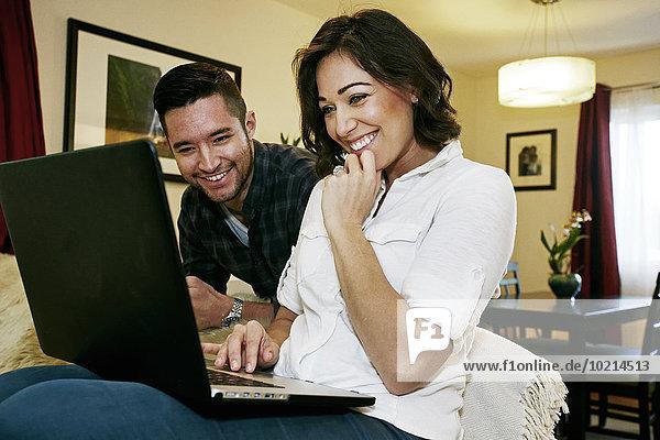 Close up of couple using laptop on sofa