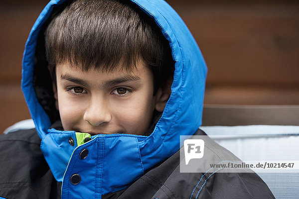 Close up of mixed race boy wearing parka and hood