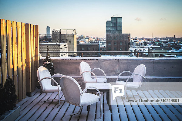 Patio furniture in snow on urban rooftop,  New York,  New York,  United States