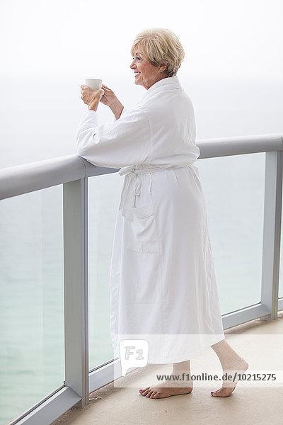 Older Caucasian woman drinking coffee on balcony