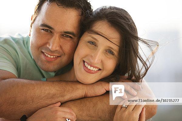 Close up of smiling Hispanic couple hugging