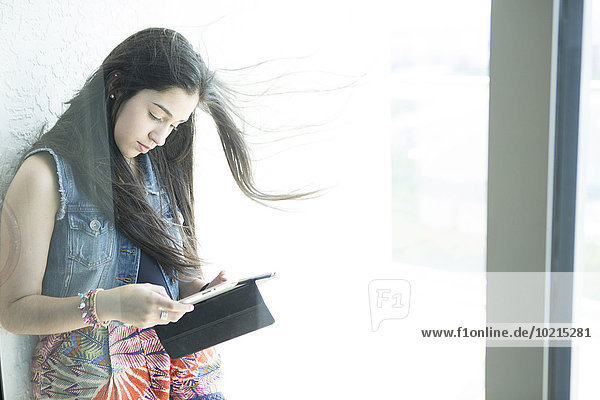 Hispanic girl using digital tablet at window