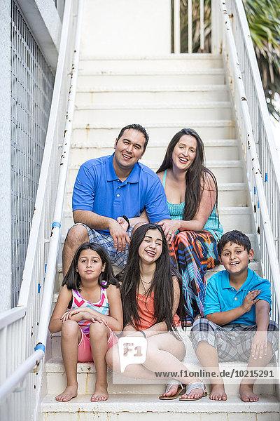 Hispanic family smiling on staircase