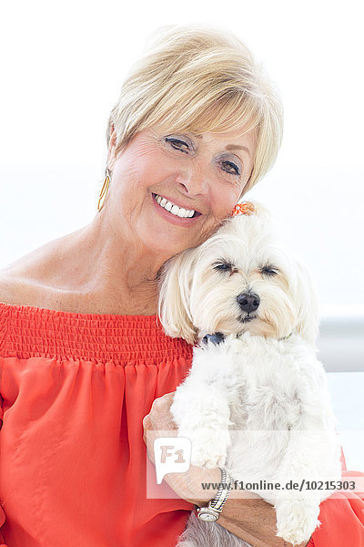 Older Caucasian woman hugging dog