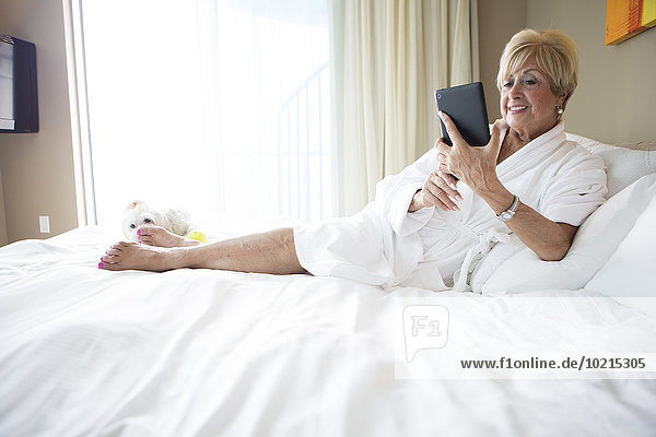 Older Caucasian woman using digital tablet on bed