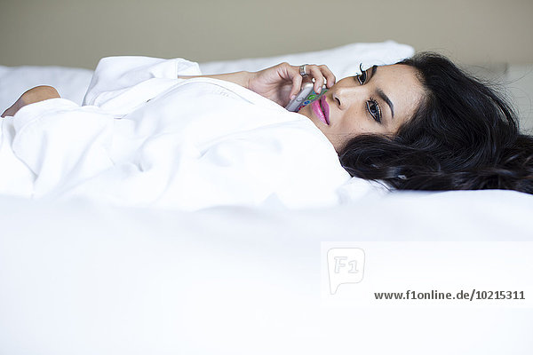 Hispanic woman talking on cell phone on bed