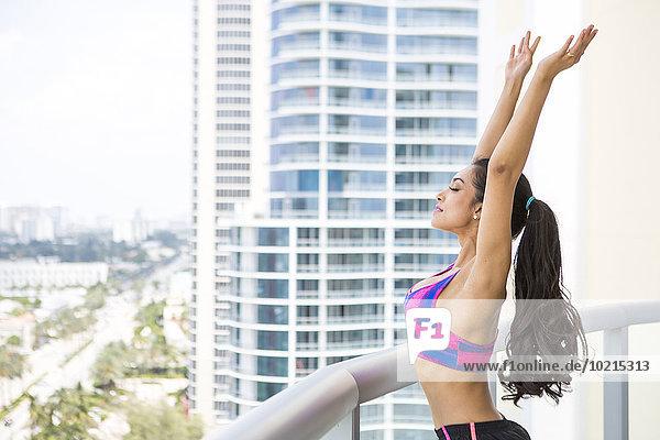 Hispanic athlete stretching on balcony