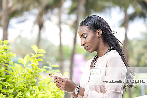 African American businesswoman using cell phone outdoors