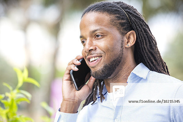 African American businessman talking on cell phone outdoors