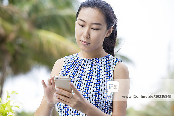 Asian businesswoman using cell phone outdoors