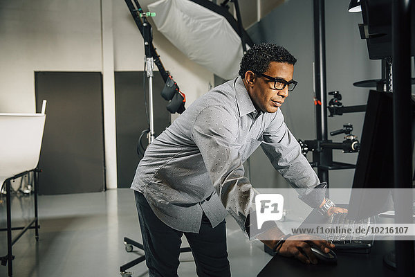Mixed race photographer using computer in studio