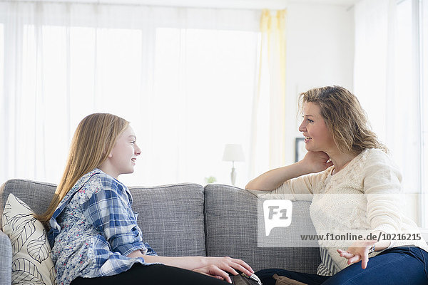 Caucasian mother and daughter talking on sofa