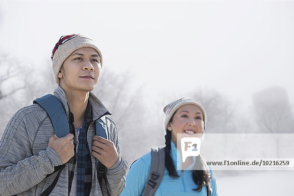 Couple hiking in snowy field