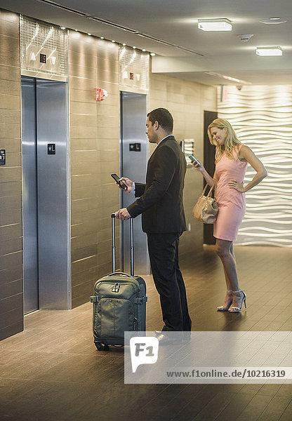 Handy benutzen Mensch Menschen warten Aufzugsanlage Business