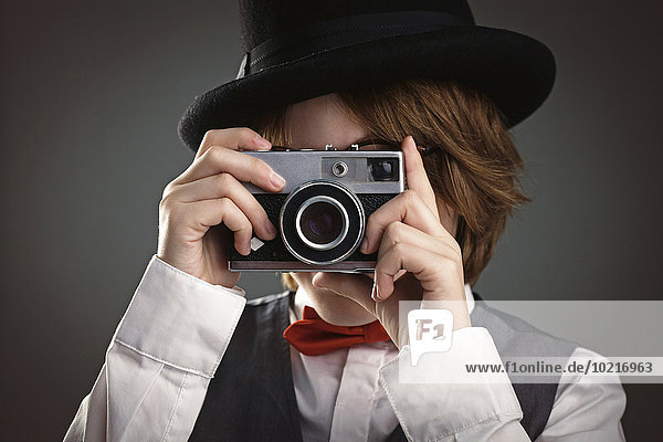 Close up of boy in top hat photographing with vintage camera