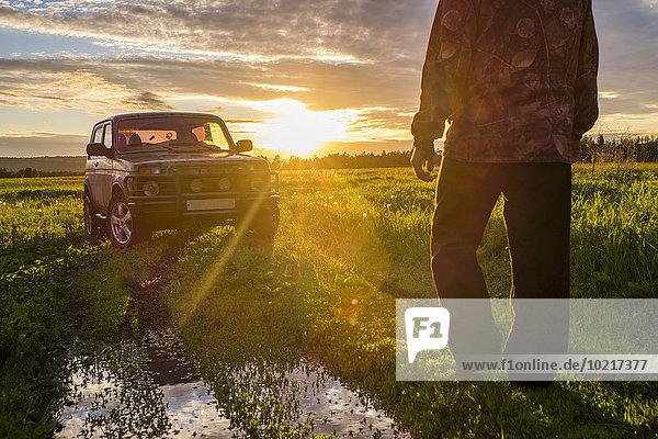 Ländliches Motiv ländliche Motive Mann gehen Feld Auto Sonnenuntergang