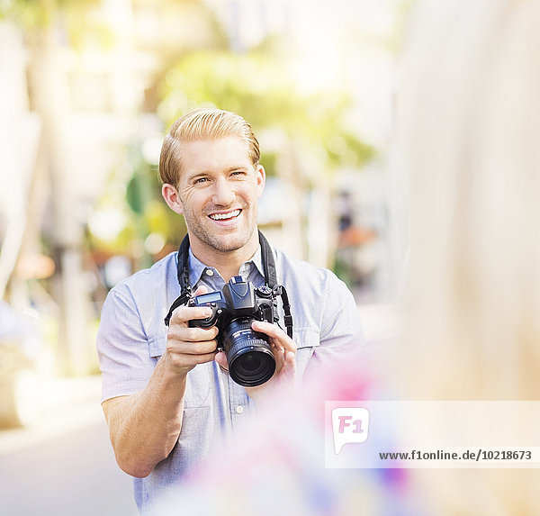 Caucasian photographer photographing woman outdoors