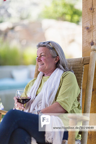Caucasian woman drinking wine on porch
