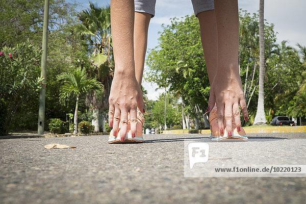 Mexiko  Nayarit  Hände und Füße eines Teenagermädchens beim Stretching auf der Straße