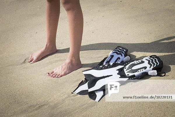 Mexiko  Nayarit  Beine von Teenagermädchen und Flossen am Sandstrand