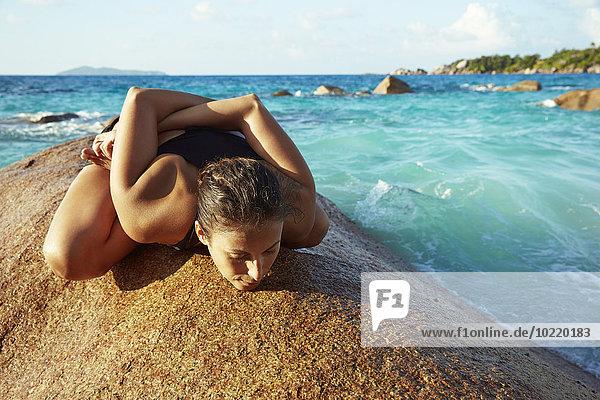 Seychellen  Frau beim Yoga auf einem Felsen