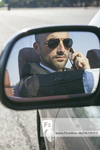 Spiegelbild des Geschäftsmannes mit Sonnenbrille beim Telefonieren im Auto