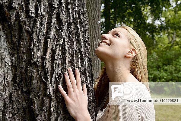 Junge Frau auf Baumstamm gelehnt