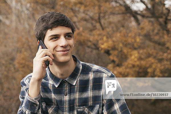 Portrait of smiling young man telephoning with smartphone in a park