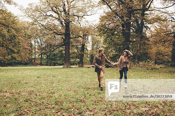 Junges verliebtes Paar hält sich an den Händen und läuft in einem herbstlichen Park.