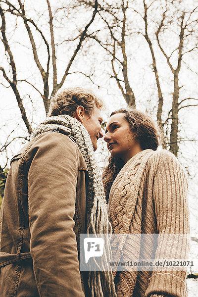 Verliebtes junges Paar steht in einem herbstlichen Park.