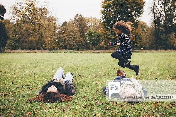 Junge Eltern liegen auf einer Wiese  während ein kleines Mädchen im Park über sie springt.