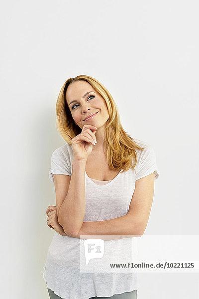 Porträt einer glücklichen jungen Frau mit der Hand am Kinn nach oben blickend