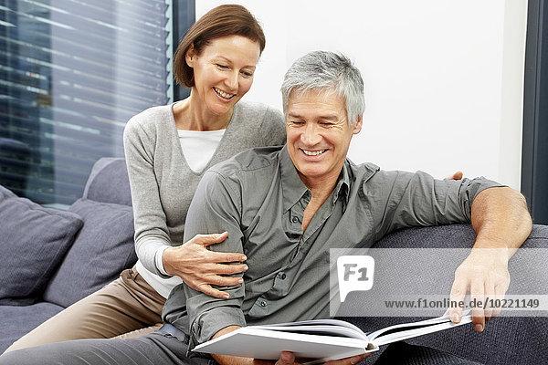 Porträt eines glücklichen Paares  das zusammen auf der Couch sitzt und ein Buch betrachtet.