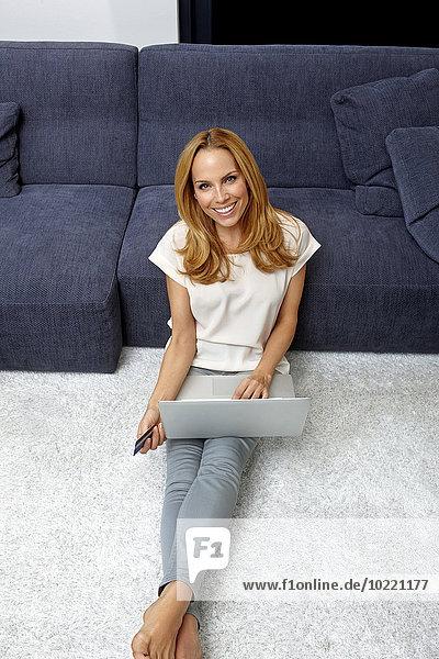 Portrait einer lächelnden jungen Frau auf dem Boden sitzend mit Laptop und Kreditkarte für Online-Shopping