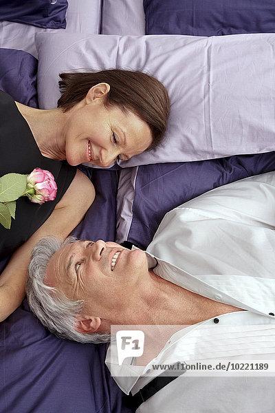Ein verliebtes Paar  das auf dem Bett liegt und sich ansieht.