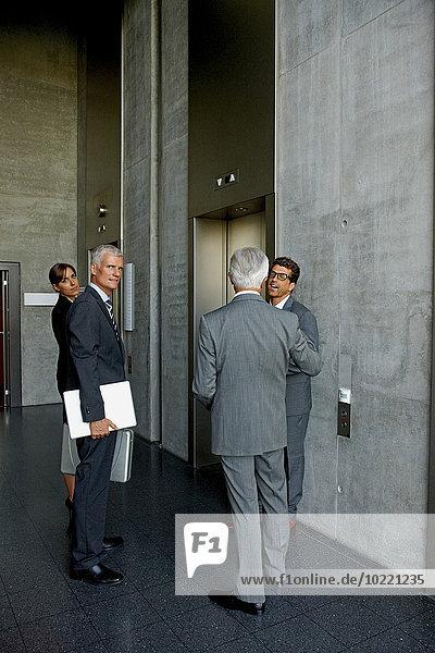 Gruppe von Geschäftsleuten im Gespräch an einem Aufzug im Büro