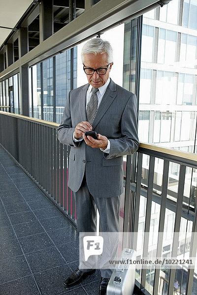 Senior Geschäftsmann steht auf dem Büroflur und schaut auf das Handy.