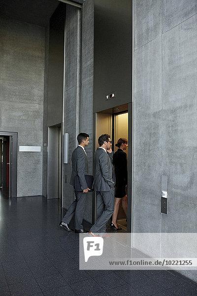 Gruppe von Geschäftsleuten  die den Aufzug im Büro betreten