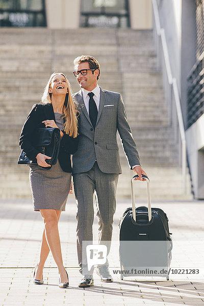 Happay Geschäftsmann und Geschäftsfrau gehen zusammen mit Koffer